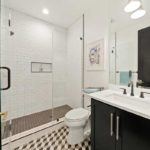 Walk in shower with a clear door and white-bricked walls. Toilet is in between shower and bathroom sync.