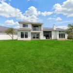 Backyard view of house. Grandiose house with fifteen windows all pointing to grassy area with trees