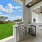 Open kitchen area with grill, dishwasher, and sync overlooking the outside grass and trees
